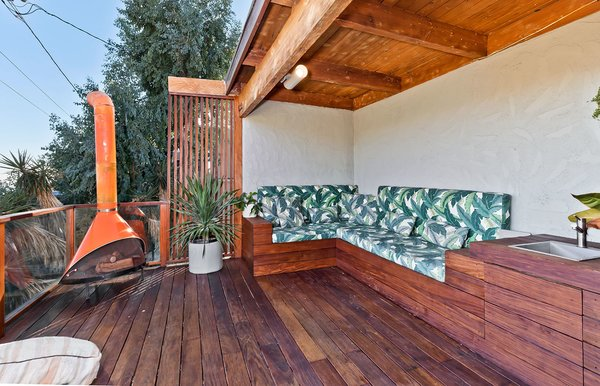 Boasting playfully upholstered bench seating and a retro orange fireplace, the partly covered deck provides an intimate place to gather and entertain.