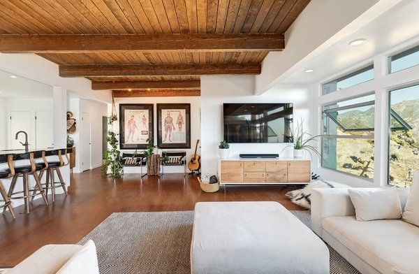 An open floor plan seamlessly weaves the home's main living areas together. Here, another look at the living room which features an exposed wood ceiling and beams.