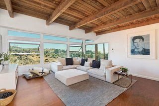 Exposed wooden beams cap the living room, which also features banks of oversized windows that open the space to Griffith Park.