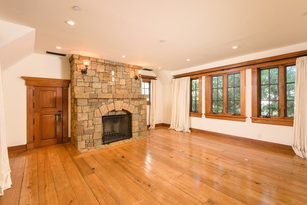A large, stone fireplace anchors the main living room. Wide-plank hardwood floors and extensive wood details run throughout the home.