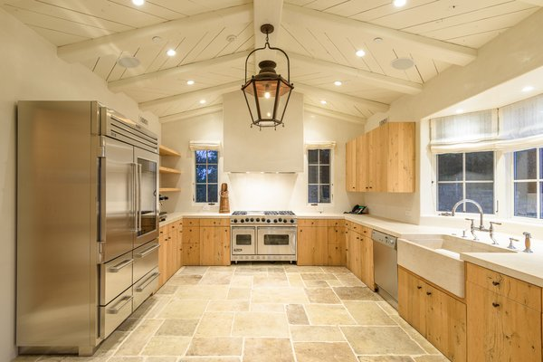 The vaulted, beamed ceilings continue into the kitchen, which is outfitted in custom cabinetry and professional-grade appliances. The room offers plenty of counter space and cabinetry for storage.
