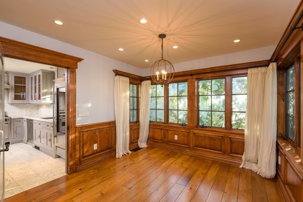 A wood-paneled dining area is located just steps away from the kitchen. Windows wrap around the space, providing views of the wooded area around the structure.