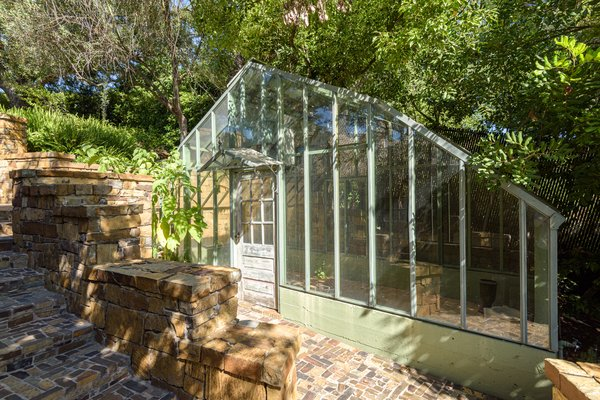 A custom-built greenhouse is situated on another side of the property.