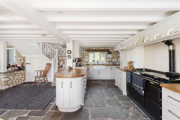 The kitchen also features a large Aga and water provided from the local spring. Wooden counters wrap around the cabinetry, capped on one end by a rounded peninsula.