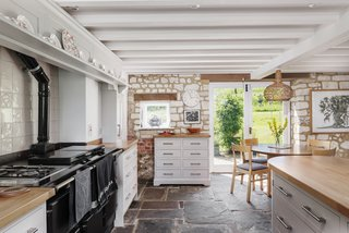A look at the kitchen, which offers a large range and an abundance of storage. Beamed ceilings, along with stone floors and walls, retain an authentic look within the space.