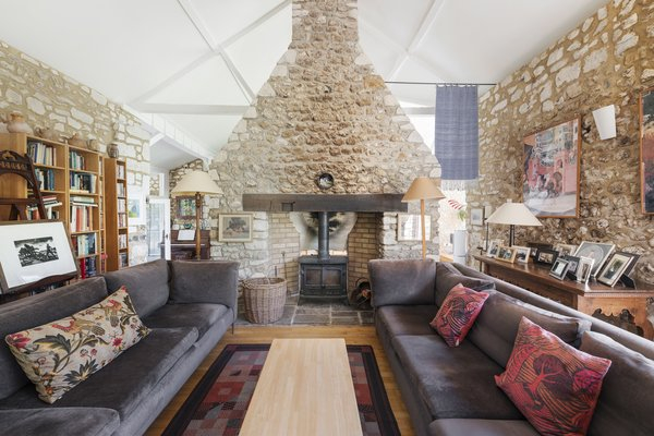 On the opposite side of the entry hall is the living room. A double fronted log burner sits within the stone chimney at the center of the space.
