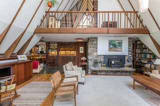 The home's main living area features cathedral ceilings and a large loft overhead. The space is divided by a stone fireplace and built-ins that lead to the kitchen.