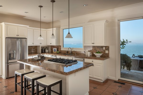 The modernized kitchen features custom cabinetry, along with stainless-steel appliances. A large picture window above the sink frames maritime views.