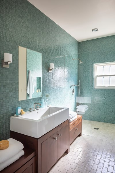 Glistening green tiles climb the walls of another one of the six full bathrooms.