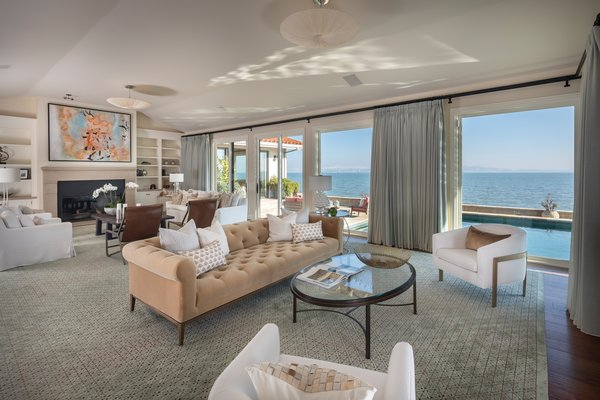 Set on a 14,000-square-foot double-lot, the single-story home offers an open-concept floor plan and several living areas. Custom bookshelves line both sides of the fireplace, while a wall of floor-to-ceiling windows provide mesmerizing bay views.