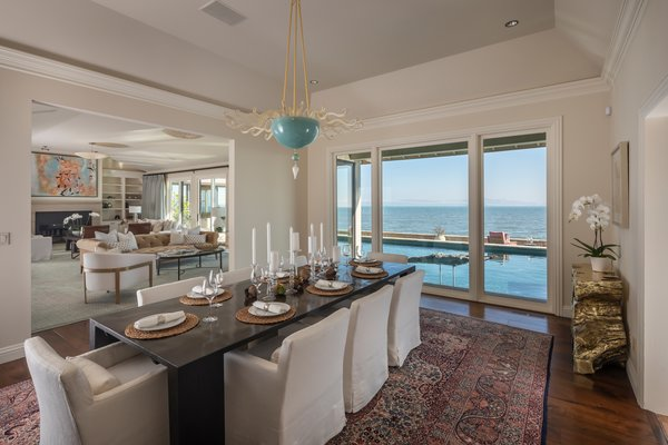 A formal dining area is located right off the main living room. Vaulted ceilings enhance the sense of space, while oversized windows overlook the pool.