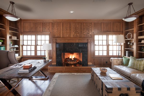 Anchored by a marble fireplace, the wood-paneled library boasts handcrafted moldings and custom-built shelving. A large wooden desk provides ample workspace.