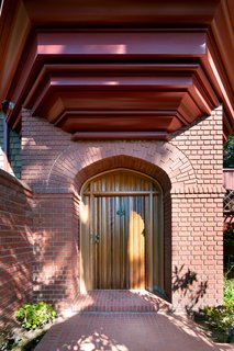 A beautiful wooden door offers a stately welcome. The polished canopy of redwood lines a bayed seating area above.