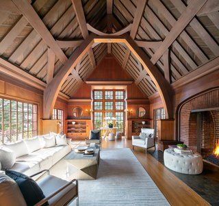 One of the home's many stunning features is its cathedral-like living area with exposed redwood beams rising over 20 feet. A large red-brick fireplace enhances the room's regal aesthetic.