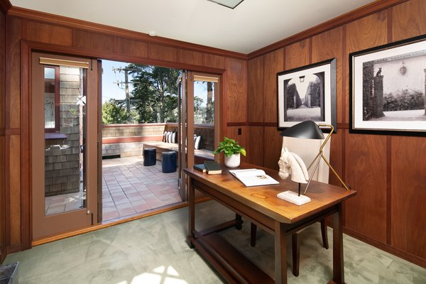 The home's extensive wood paneling continues into a small office next to the kitchen. This space also provides access to the side terrace.