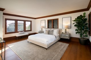 In total, the home includes four bedrooms, all of which benefit from the home's many windows. A leaded glass window above the headboard originally looked down into the living room.