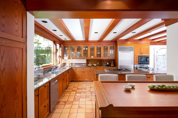 The open-concept kitchen offers modern conveniences while retaining much of its original detailing, including the custom cabinets and exposed ceiling beams. A picture window stretches across the countertops along one wall.
