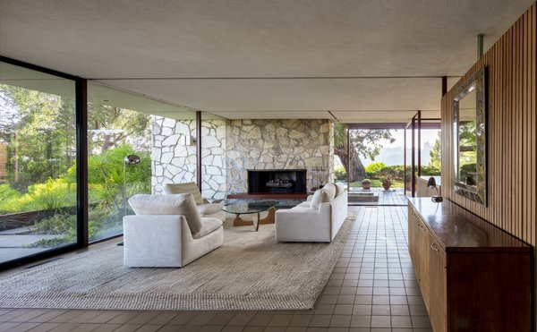 In the living room, an original natural rock fireplace continues through the glass to divide the patio.