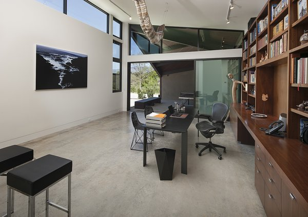 An office space is located in a second pavilion. Similar to the other areas, a sliding door opens the room to a private patio, while the sloping roofline rises up to meet clerestory windows that drench the space in natural light.
