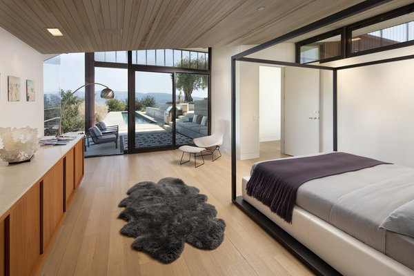 In the sleeping pavilion, the master bedroom looks out onto the 70-foot lap pool and expansive views of the surrounding mountains. Built-in cabinetry, expansive fenestration, and a harmonious color palette define the calming space.