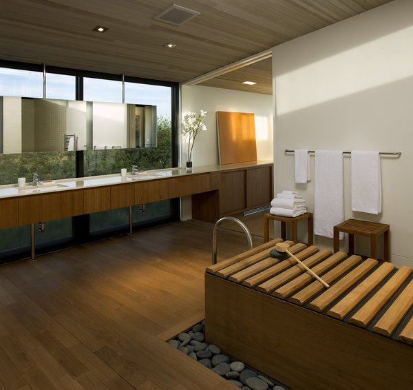 The master bathroom offers a spa-like atmosphere, with a floating vanity and mirror, along with the use of natural materials such as wood and stone. A large picture window creates a serene backdrop for the space.