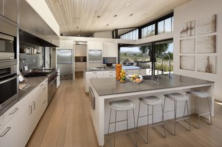 A look at the large kitchen, which offers numerous high-end appliances and two large islands. Large sliding glass panels create a connection with the surrounding landscape and opens the space to a patio. Interior designer Brad Dunning originally collaborated on the dwelling.