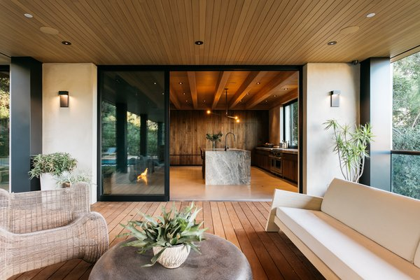 A covered wooden deck is located off the kitchen. The indoor/outdoor connection is enhanced by large sliding doors that seamlessly connect the two spaces.