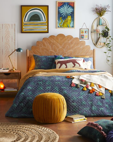 A Bohemian Carved Wood Headboard pairs with the Jungle Leopard Quilt Set and a Rainbow Pom Decorative Throw.