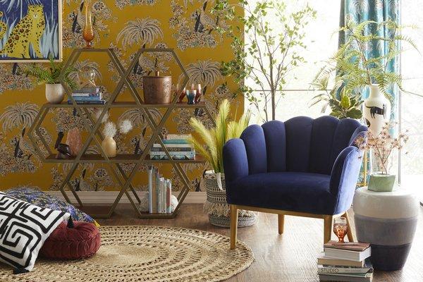A Petal Accent Chair adds a bit of luxe next to an airy Hexagon Bookshelf.