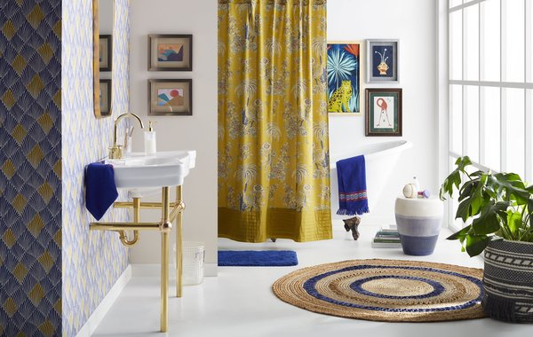 A Tropical Toile Shower Curtain and a Round Blue Stripe Jute Area Rug bring a touch of island style into the bathroom.