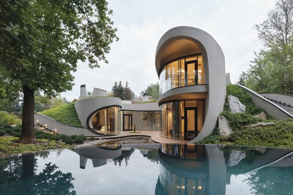 Niko Architect and landscape firm Ecopochva designed a Moscow home that doesn't play by the rectilinear rules of conventional architecture. Vegetation blankets the home's concrete form, and its walls sweep upward and outward to become roofs. Molded floor-to-ceiling windows curve to grant panoramic views of the backyard and swimming pool.