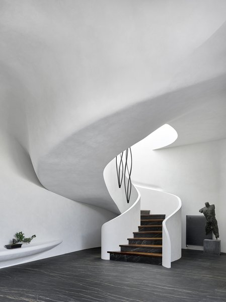 A sweeping staircase spirals up to the second floor. A sculpture plays off the black marble floors, and a bonsai perches preciously on a rounded display ledge.