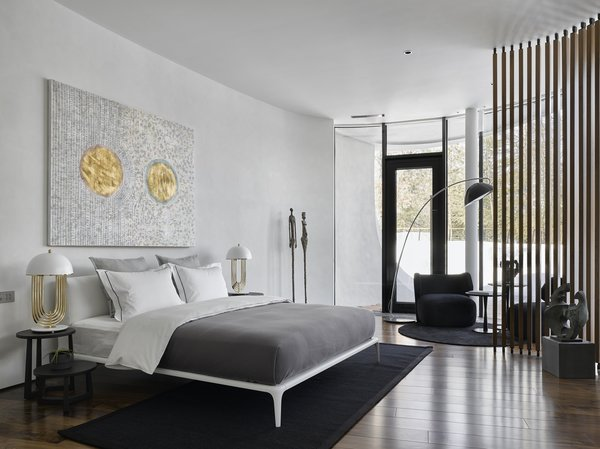 Downstairs, the bedroom features wood flooring and vertical wooden slats that provide privacy from the courtyard. Accents of gold and black play off the white walls.