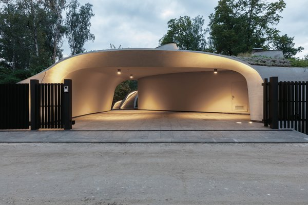 An asymmetrical, futuristic, and seductively lit carport faces the street, looking a bit like a set from Star Wars' Cloud City.
