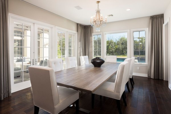 The formal dining area overlooks the backyard pool. French doors lead directly to the home's spacious courtyard patio, which sits sandwiched between the dining and living rooms.