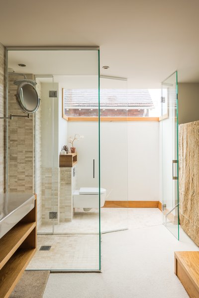 The modern bathroom features floating vanities, a curbless shower, and a glass-encased loo. A wide clerestory window fills the entire space with natural light.