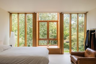 One of two bedrooms on the first level, the master bedroom sits at the back of the addition. A series of vertical window panes run from floor-to-ceiling and across the entire space, framing views of the treetops and looking out over the lush backyard.