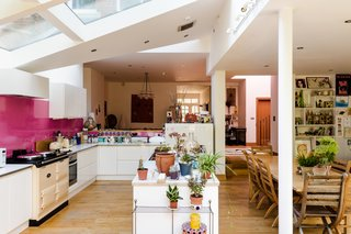 The large kitchen sits beneath several broad glass panels along the ceiling. The contemporary space is open on three sides, finished in simple white cabinetry with a pop of color along the backsplash.