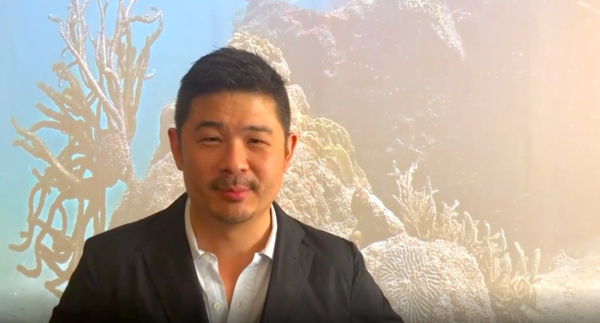 Design Miami's curatorial director, Aric Chen, in front a work by Coral Morphologic, a Miami duo who have placed a live webcam in a coral reef that is thriving in the busy urban waters of Biscayne Bay.