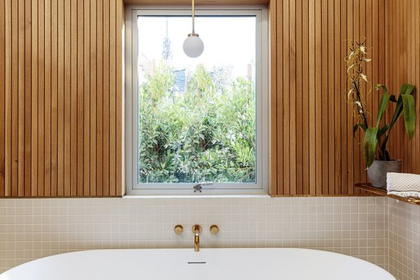 Wood slats wrap the master bath walls, bringing in a touch of warmth and contrasting texture.