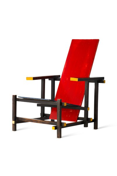 """The Dutch architect and cabinetmaker Gerrit Rietveld designed the precursor to his famous Red Blue Chair in 1918/1919. He submitted the unpainted model to an exhibition at the Museum for Applied Arts in Haarlem, which included a competition for the best design for a simple lounge chair that could be manufactured for less than 35 guilders—roughly $20. The resulting design is an open spatial composition, corresponding to the principles of the De Stijl movement, of which Rietveld was a member. """"The construction helps to interconnect the components without mutilating them or allowing one to dominate the other, with the resulting effect that the whole stands free and clear within the space and the form is further emphasized by the material,"""" he says."""