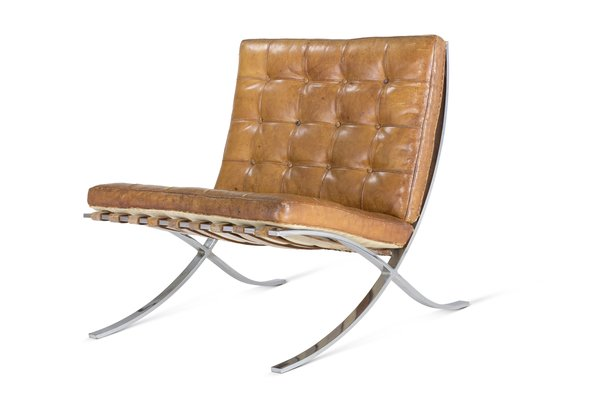 The Barcelona chair was designed by Mies van der Rohe and Lilly Reich for the German Pavilion at the International Exposition of 1929 in Barcelona, Spain. The frame was initially designed to be bolted together, but it was redesigned in 1950 using a seamless piece of stainless steel for a smoother appearance. The ivory-colored pigskin used for the original pieces was eventually replaced with bovine leather.