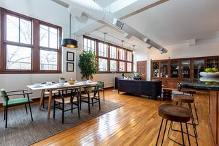 Newly restored hardwood floors and wooden trim run throughout the space, adding a warmth to the traditional industrial loft style. Bright upholstered chairs add a colorful touch, complementing the lush greenery throughout the space.