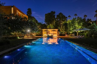 The pool house gleaming with light at night.