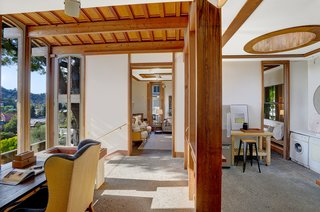 Inside the modern addition, a small office in the entranceway overlooks the garden and scenic views. Wood details run throughout the stand-alone space, which includes a separate living room and kitchen, as well as a bedroom and bathroom.