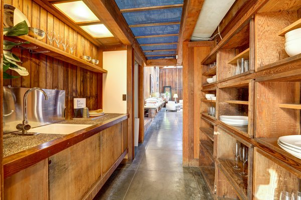 At one end of the space, a galley-style kitchen offers redwood cabinetry and shelving. The mostly original space has been upgraded with granite countertops and some new fixtures.