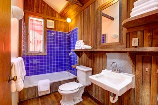 A look at the only full bathroom in the original structure. The space features the original redwood paneling with updated fixtures and finishes.