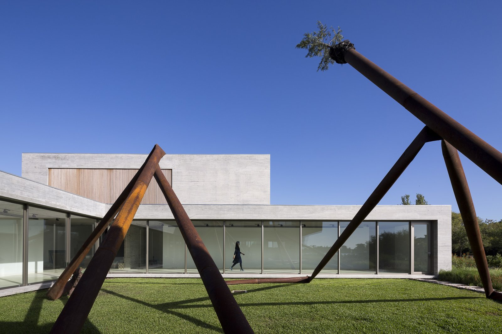A large sculpture made of weathered metal stands in the home's central yard.