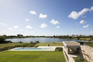 The Island House's large, grassy backyard overlooks a nearby lake ringed with trees.
