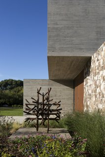 A weathered metal sculpture at the front door echoes the larger piece in the home's central yard.